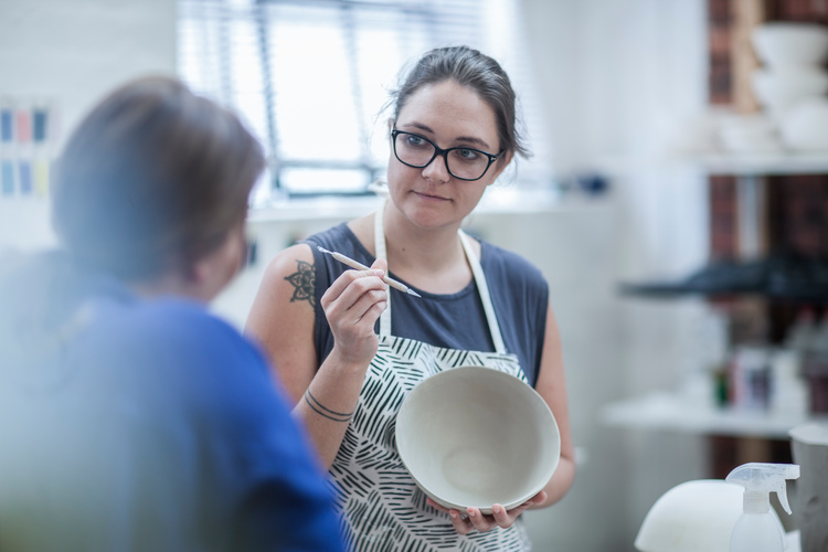 Cape Town, South Africa, young female and co worker showing off her bowl made from clay in ceramic workshop
